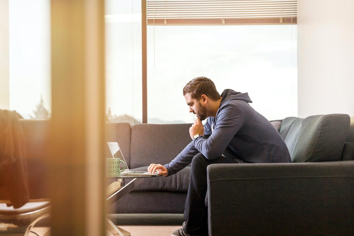 Henkilö työskentelee tietokoneella sohvalla
